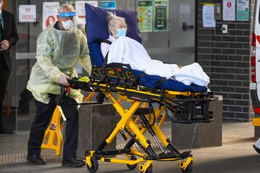 Los trabajadores médicos evacuan a una residente del centro de cuidado de ancianos Epping Gardens en Melbourne el 30 de julio de 2020