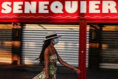 Una mujer pasea por el puerto de Saint-Tropez el 16 de agosto de 2020 con mascarilla, ya que la ciudad hizo obligatorio el uso de tapabocas en el centro de la ciudad debido a un resurgimiento del coronavirus