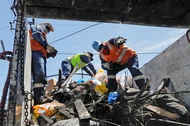Los voluntarios llenan camiones con la basura que quedó tras los incidentes.