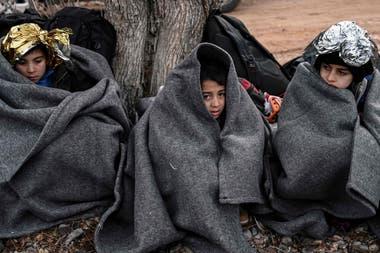 Niños con mantas se sientan en la playa después de que un bote con 54 refugiados afganos desembarcó en la isla griega de Lesbos