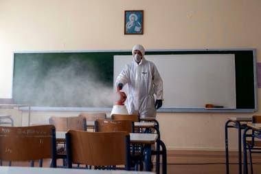 Un trabajador rocía desinfectante en un aula en Ioannina, Grecia