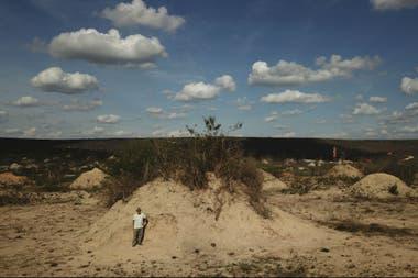 El botánico estadounidense Roy Funch posa junto a un montículo de termitas cerca de Barauna, Brasil
