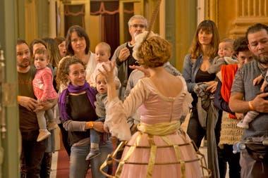 Madres y padres esperan en el foyer de ingreso al teatro Colón, mientras se toman selfies con sus niños, que no superan los dos años