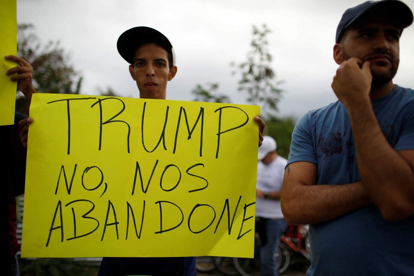 Venezolanos con carteles, frente a los galpones con la ayuda humanitaria en Cúcuta