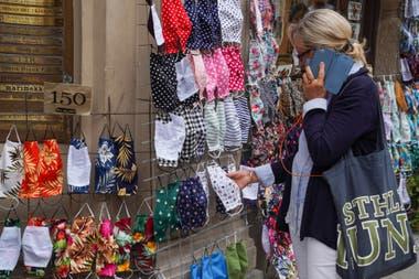Una mujer mira un negocio de tapabocas en el centro de Estocolmo, el 31 de agosto pasado