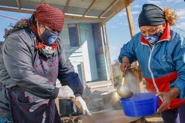 Araceli y Sandra se ocupan de servir las raciones en los potes previamente sanitizados