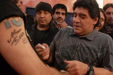 Maradona firma autógrafos a la salida de un programa de TV, en 2009