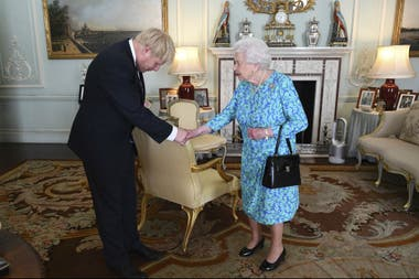 Boris Johnson junto a la reina