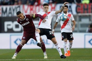 Martínez Quarta lucha por la pelota con Sand, en un partido de la actual Superliga