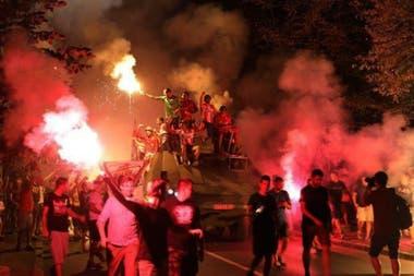 Los apasionados hinchas de Estrella Roja portan bengalas mientras siguen al tanque con los jugadores