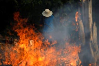 Un granjero camina entre las llamas que afectan a gran parte del Amazonas
