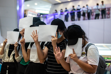 Los manifestantes tapan sus caras con papeles en blanco durante una protesta por la nueva ley de seguridad en un centro comercial en Hong Kong el 6 de julio de 2020