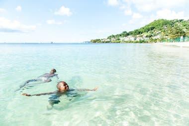 Dos personas disfrutan del agua cristalina de las costas de Grenada