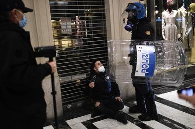 Agentes de la policía italiana detienen a un activista de extrema derecha durante una protesta contra las medidas de restricción del gobierno para frenar la propagación del coronavirus, en el centro de Turín, el 26 de octubre de 2020