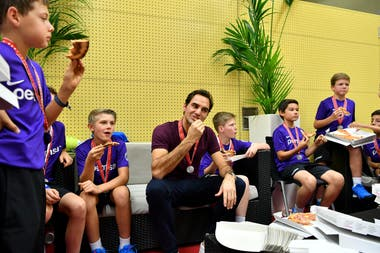 Roger Federer comparte una pizza con los ball boys