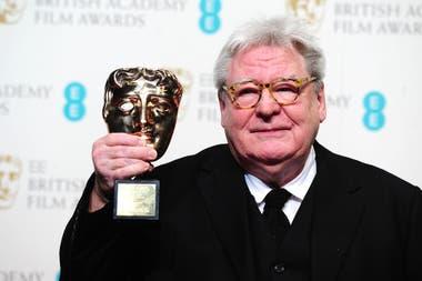 Alan Parker alza el premio honorífico que le dio la Academia de cine británica, en 2013