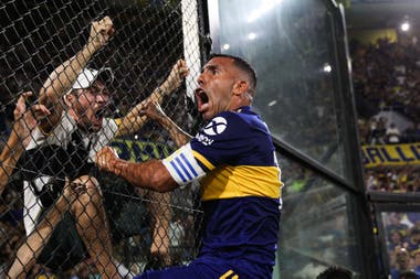Carlos Tevez y un gol que valió un título. Lo celebra con una postal que tardará en repetirse por cuestiones sanitarias: subido al alambrado y cara a cara con los hinchas.