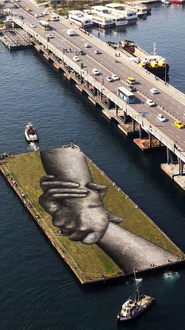 """Una vista aérea muestra una obra del artista callejero franco-suizo Saype llamada """"Beyond Walls"""" en una barcaza flotante sobre el Cuerno de Oro en Estambul, Turquía"""