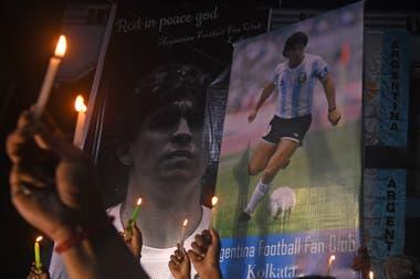 Los fanáticos sostienen velas mientras rinden homenaje a la leyenda del fútbol argentino Diego Armando Maradona en Calcuta el 26 de noviembre de 2020