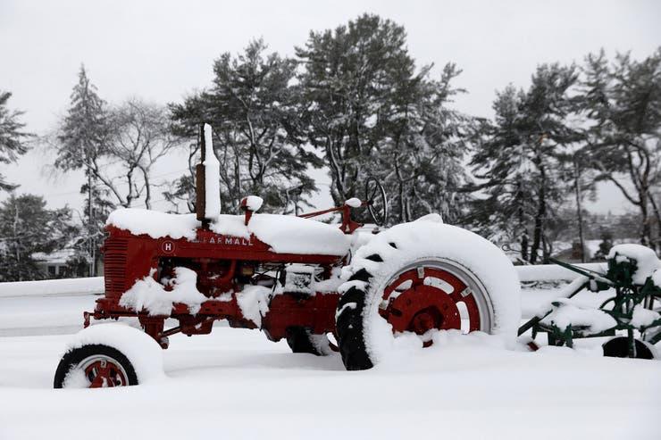 Un tractor en medio del campo cubierto de nieve