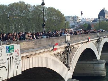 Turistas y locales observan desde el puente de Austerlitz, sobre el Sena, el derrumbe de la catedral por el voraz incendio