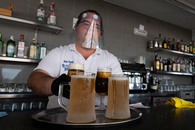 Un camarero con un protector facial prepara algunas cervezas para servir en la terraza del bar La Malvarrosa en Valencia, el 19 de mayo de 2020, ya que algunas provincias españolas pueden aliviar las restricciones de bloqueo en medio del coronavirus