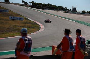 Los oficiales de pista observan al piloto alemán de Ferrari, Sebastian Vettel, durante la tercera sesión de práctica en el Autodromo