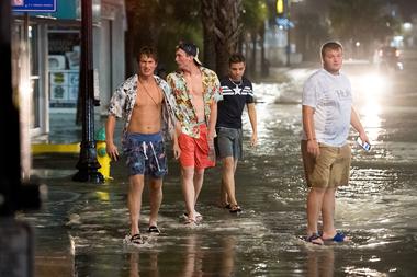 La gente camina en medio de las inundaciones en Ocean Blvd. el 3 de agosto de 2020, en Myrtle Beach, Carolina del Sur