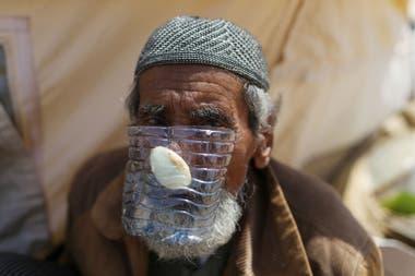 Un anciano gazatí cubrió su rostro con un envase plástico y una cebolla