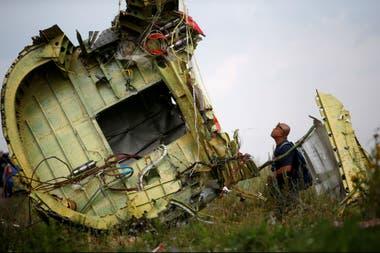 Un investigador estudia un pedazo del avión en Hrabove, en 2014