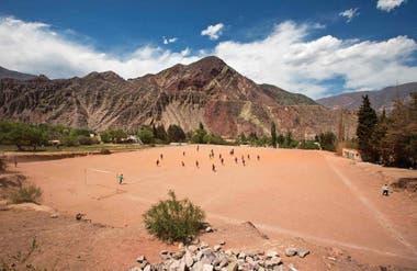 Partido de fútbol en un potrero de Purmamarca, rodeado de cerros.