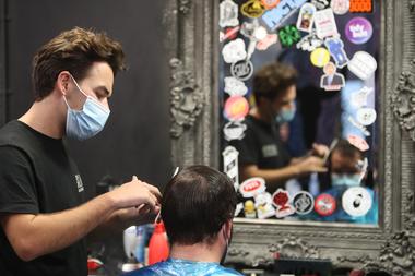 Un peluquero corta el pelo de un cliente en Cardiff, Gales del Sur, el 20 de octubre de 2020, antes de un breve cierre de dos semanas que comenzará el 23 de octubre, después de que los casos del nuevo coronavirus comenzaron a aumentar nuevamente