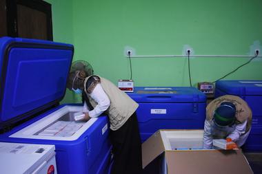 Los trabajadores de la salud empacan contenedores de vacunas contra la Covid-19 producidas por Sinovac de China, en una cámara fría en Bandung, Indonesia, el 13 de enero de 2021