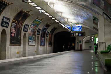 Un hombre se sienta en una plataforma desierta de una estación de metro, el 17 de octubre de 2020 en París, al inicio de un toque de queda nocturno implementado para combatir la propagación del coronavirus