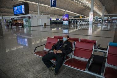 Una persona espera su vuelo en el desierto aeropuerto de Hong Kong; los casos importados y los pacientes asintomáticos generan un rebrote del coronavirus en China