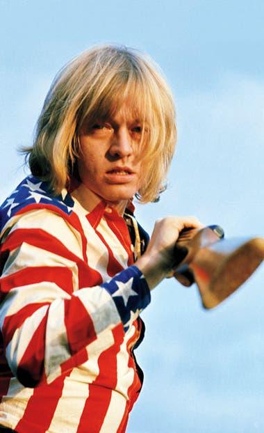 """El fundador y guitarrista de los Stones Brian Jones en su casa de East Sussex, Inglaterra, en 1969, poco tiempo antes de morir en julio de ese año. Jones se puso la camisa con la bandera de manera espontánea, y agarró el rifle. """"Probablemente estaba de resaca"""", dice Russell"""