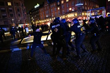 """Un grupo de manifestantes que se hacen llamar """"Hombres de Negro"""" se enfrentan a la policía mientras se manifiestan contra las restricciones del coronavirus en la plaza del ayuntamiento y en las calles laterales que conducen a la plaza de Copenhague el 9 de enero de 2021"""