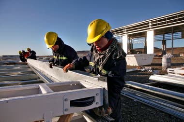 Obreros trabajan en la construcción de galpones