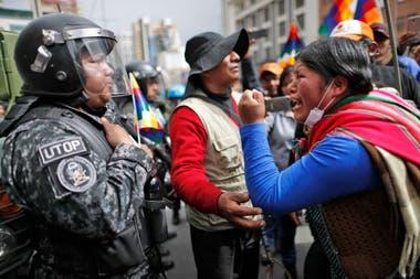 Una mujer seguidora del ex presidente de Bolivia, Evo Morales, le grita a un oficial de policía y le dice que respete a los pueblos indígenas de la nación