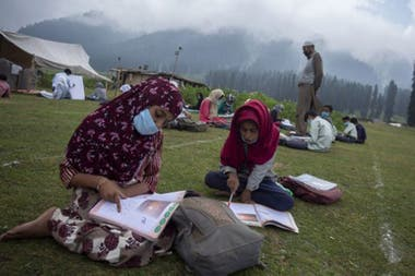 El mundo entero está discutiendo la reanudación de las clases presenciales; arriba, escuela al aire libre en Cachemira.