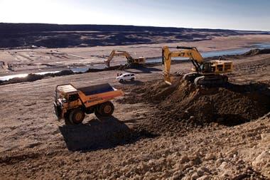 Camiones de gran tamaño, utilizados en minería, extraen el material a la vera del río