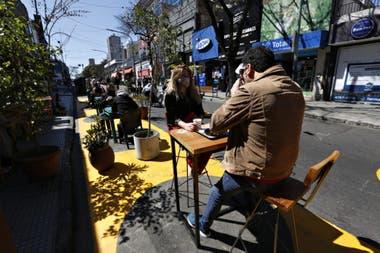 Fernando Grone y Cecilia Mitigueri toman un café sobre una de las mesas de la calle con demarcaciones para la distancia social