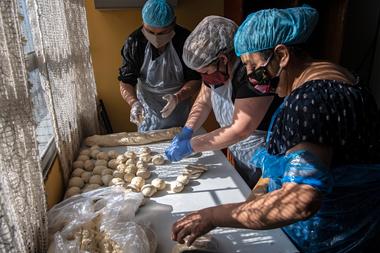 Voluntarios preparan el almuerzo en un comedor popular en el barrio de La Pintana, Santiago, el 25 de mayo de 2020, en medio de la pandemia de coronavirus