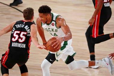 6 de septiembre de 2020; Lake Buena Vista, Florida, Estados Unidos; El alero de los Milwaukee Bucks, Giannis Antetokounmpo (34), regatea al escolta del Miami Heat, Duncan Robinson (55), durante la primera mitad del cuarto juego de la segunda ronda de los Playoffs de la NBA 2020 en ESPN Wide World of