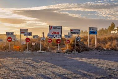 Acaso la esquina de Añelo más fotografiada: los carteles indican las distintas áreas de explotación; cada vez hay más