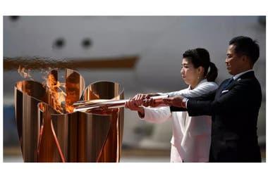 Los antiguos campeones olímpicos Saori Yoshida y Tadahiro Nomura encienden el pebetero de los Juegos de Tokio con la llama olímpica tras bajar del avión en que la trajeron de Grecia, el 20 de marzo de 2020 en la base áerea de Higashimatsushima (Japón)