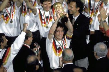 Lothar Matthaus, el capitán de Alemania, eleva la Copa del Mundo tras la final de Italia 90; Franz Beckenbauer se convierte en uno de los pocos campeones como futbolista y como seleccionador.