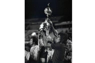 Jorge Ribolzi de Boca Juniors, al frente, sostiene el trofeo después de la tanda de penales de la final de la Copa Libertadores de fútbol contra el Cruzeiro de Brasil en Montevideo, Uruguay, el miércoles 14 de septiembre de 1977.
