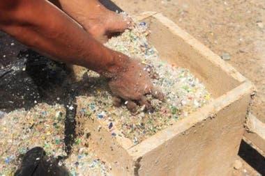 Las botellas, que son la materia prima para elaborar el concreto, se trituran para formar bolas y se lleva a la obra en enormes bolsas negras