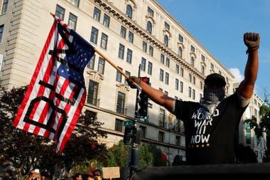 """Un hombre marcha en Washington con una bandera con las siglas del movimiento internacional """"Black Lives Matter"""""""